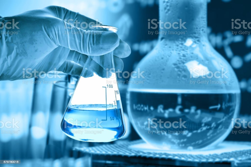 Flask in scientist hand with lab background stock photo