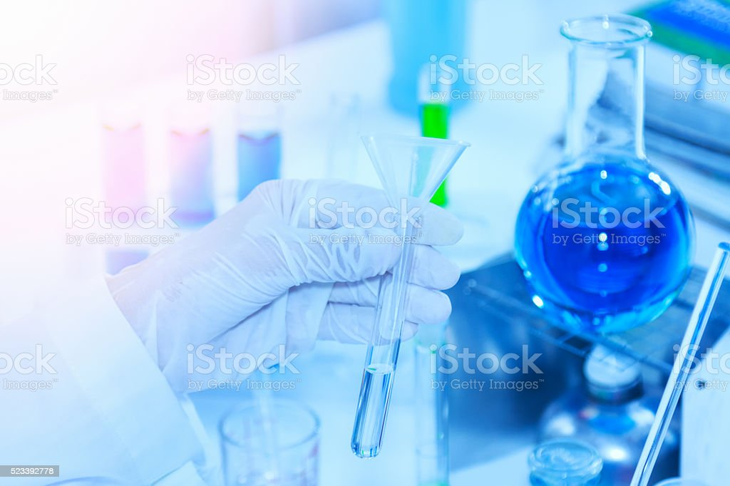 Flask in scientist hand with test tubes for analysis. stock photo