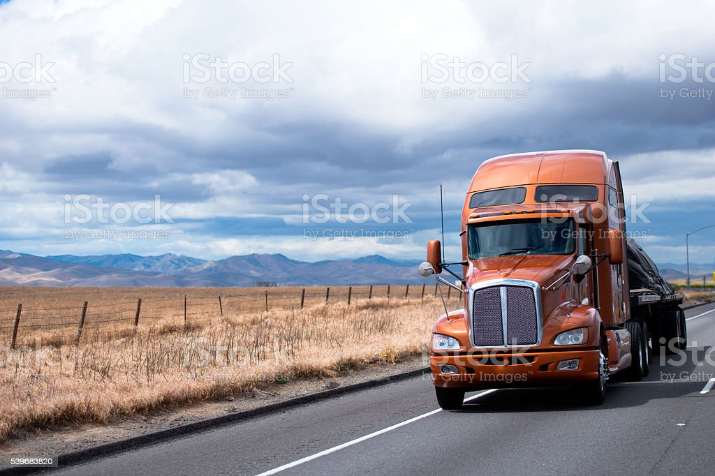 Flat bed semi truck transporting cargo under cover on road stock photo