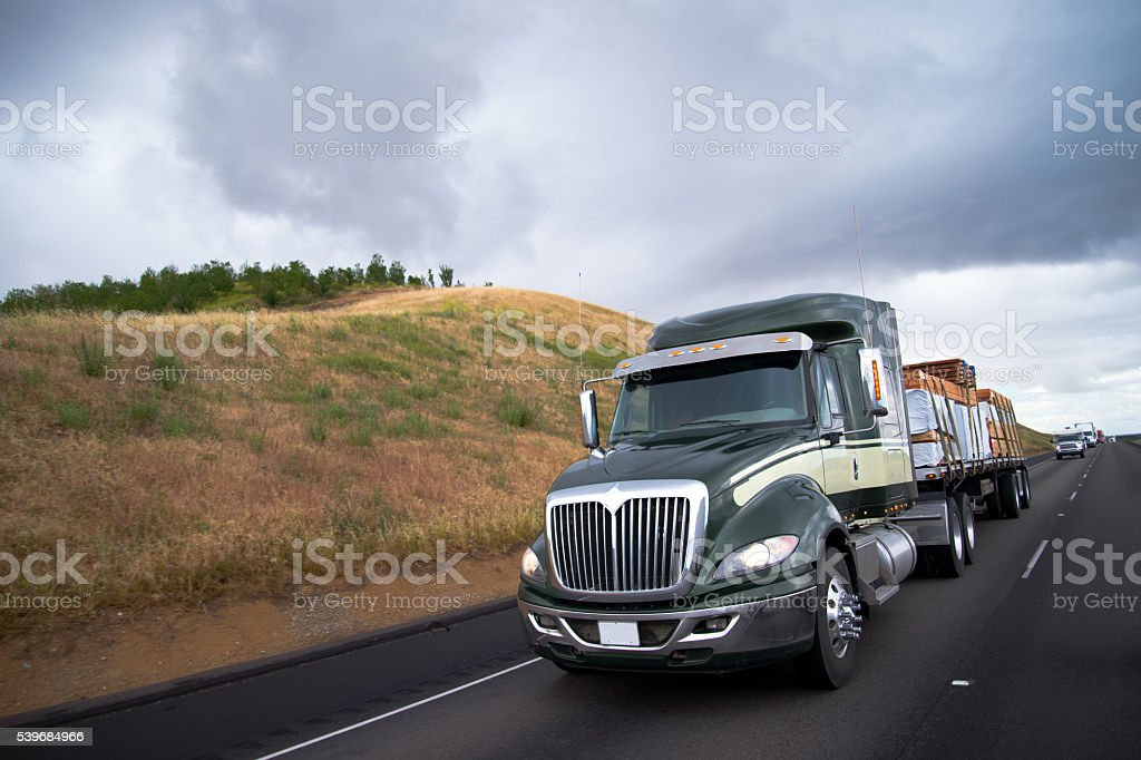 Flat bed semi truck transporting lumber cargo on California road stock photo