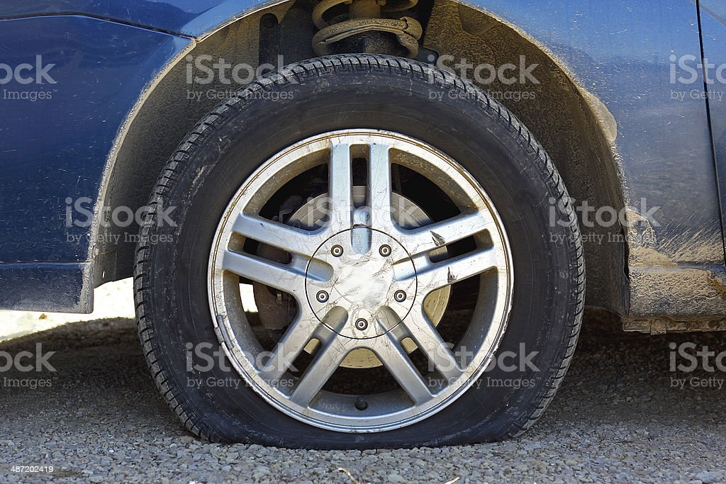 Flat Car Tire on Gravel Road stock photo