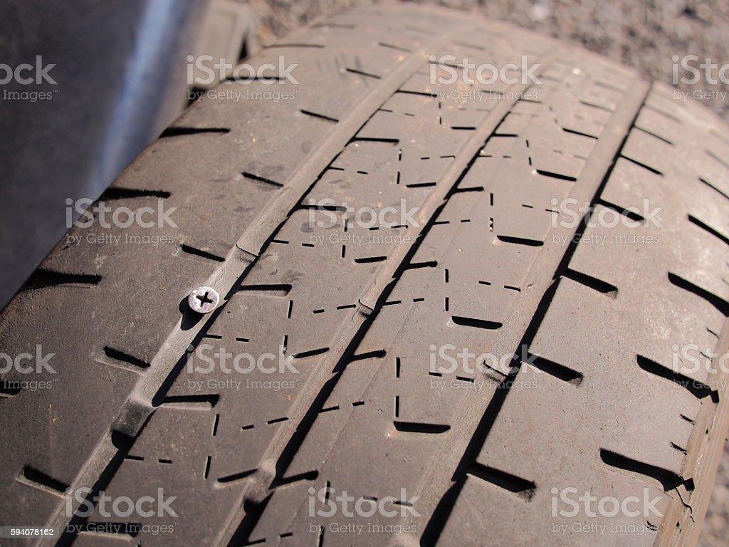 Flat car tire with a silver screw pierced through stock photo
