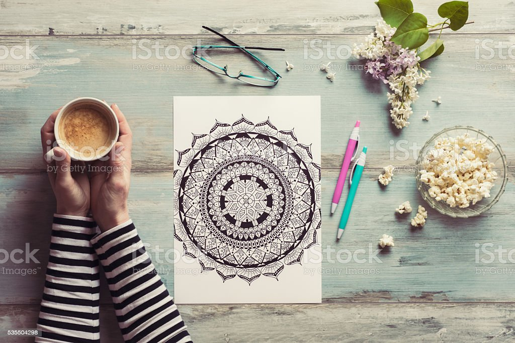 Flat lay, female coloring adult coloring books, stress relieving trend stock photo