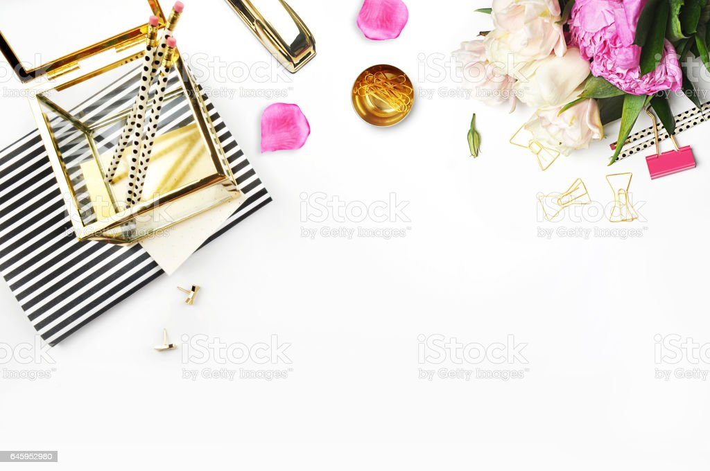 Flat lay. Flower on the table.Gold stapler. Table view. Mock-up background. Peonies. Stationery. Stripe notebook with gold box. stock photo