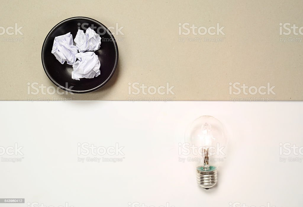 flat lay - light bulb crumpled paper background stock photo