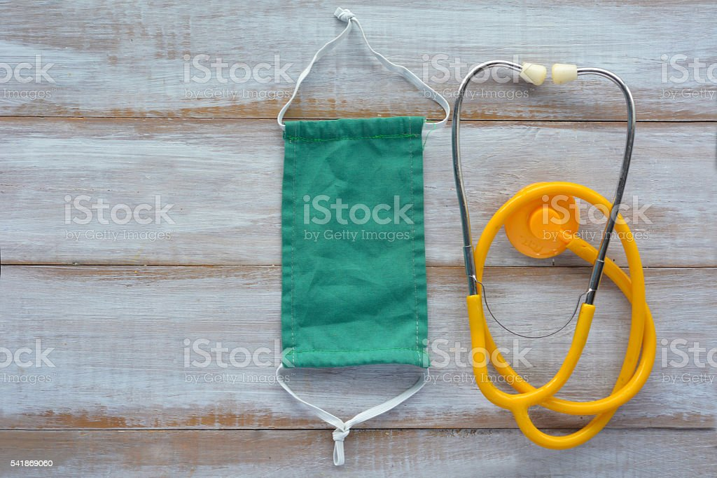 Flat lay of a Doctors stethoscope and surgical mask stock photo