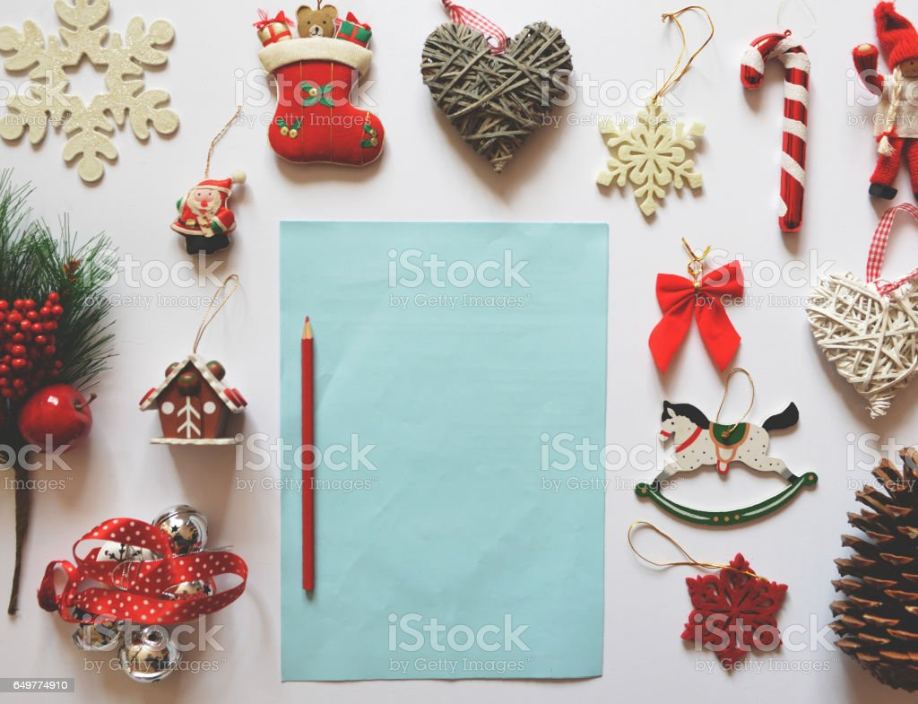 Flat lay of Christmas decoration ornaments on white background and blank paper with pen - Letter for Santa concept stock photo