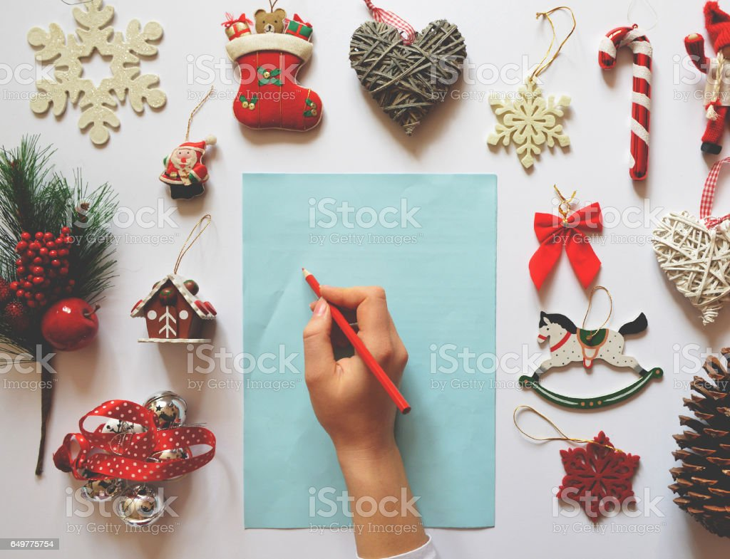 Flat lay of Christmas decoration ornaments on white background and girls hand writing on blank paper  - Letter for Santa concept stock photo