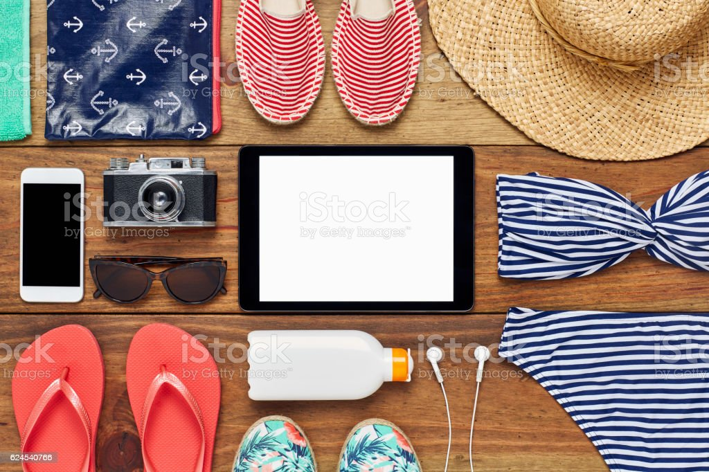 Flat lay of digital tablet surrounded with beach accessories stock photo