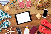 Flat lay of digital tablet surrounded with beach accessories