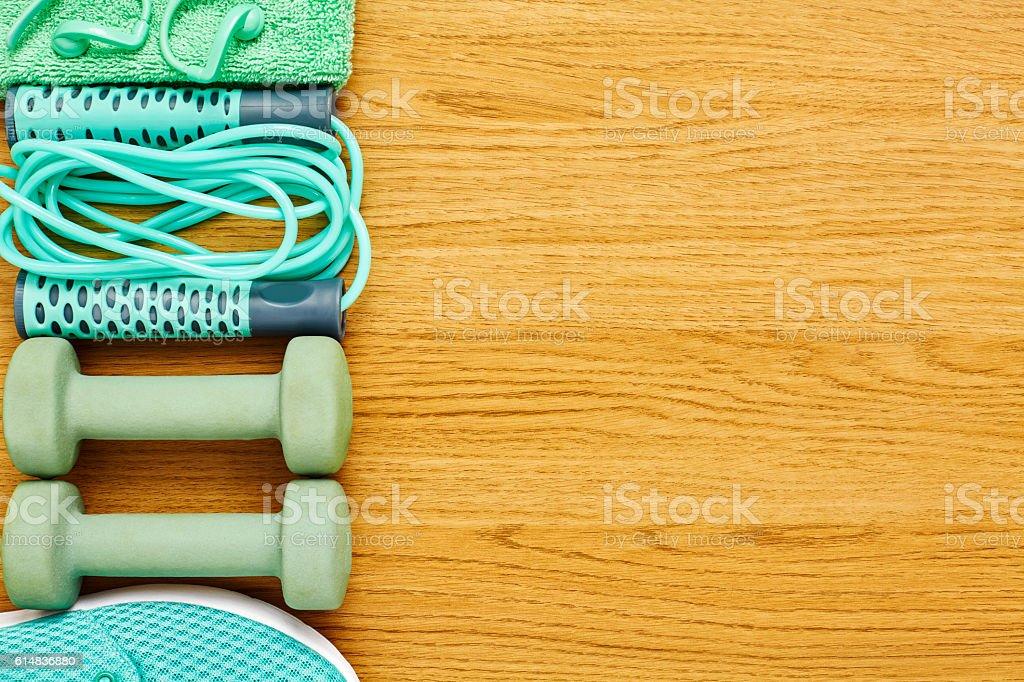 Flat lay of exercise equipment arranged on hardwood floor stock photo