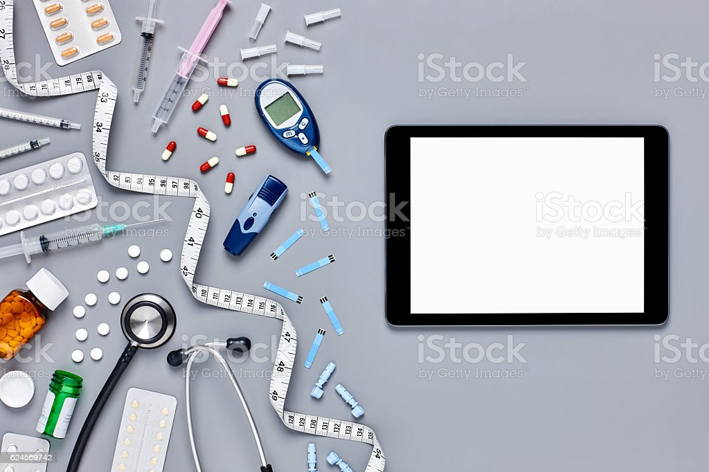 Flat lay of medical supplies and computer on gray background stock photo