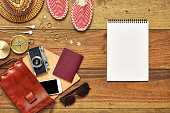 Flat lay of note pad by summer vacation accessories