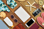 Flat lay of note pad surrounded with beach travel accessories