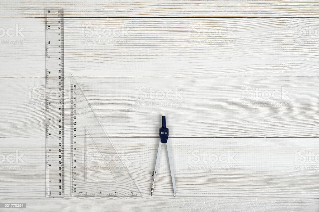 Flat lay of riangle centimeter rulers and engineering divider on stock photo