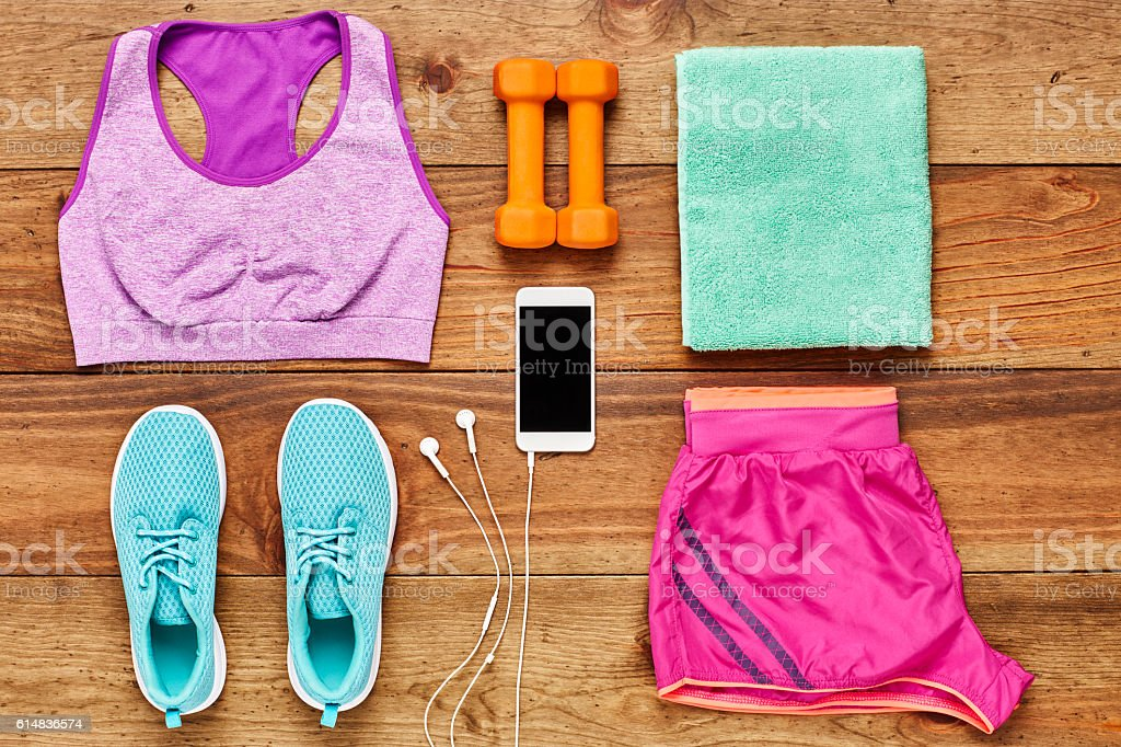 Directly above flat lay shot of smart phone with dumbbells and sports...