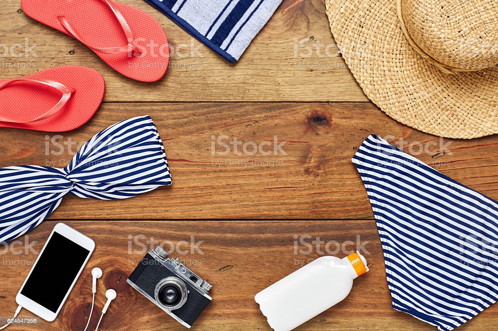 Flat lay of summer vacation accessories on hardwood floor stock photo