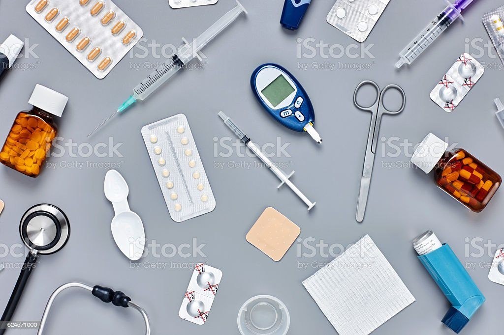 Flat lay of various medical supplies arranged on gray background stock photo