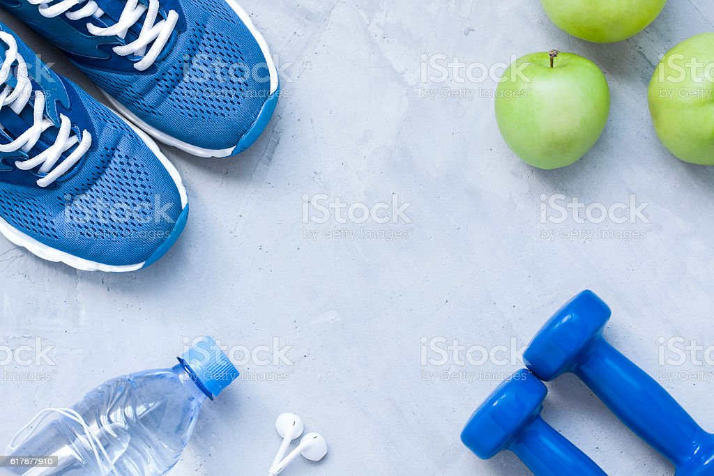 Flat lay sport shoes, dumbbells, earphones, apples, bottle of water stock photo