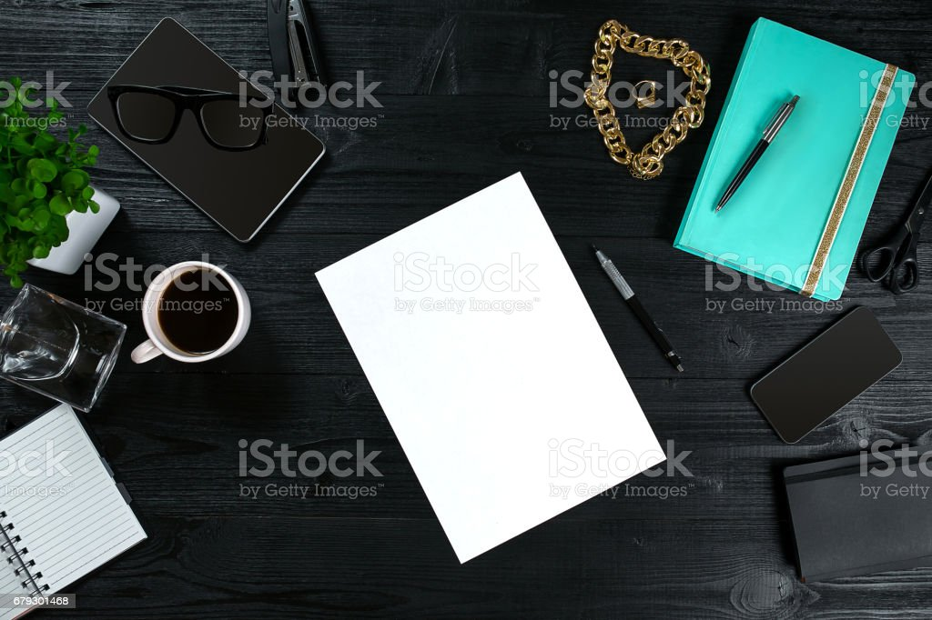 Flat lay, top view office table desk frame. Workspace with clean sheet of paper, mint diary and mobile device on dark background stock photo