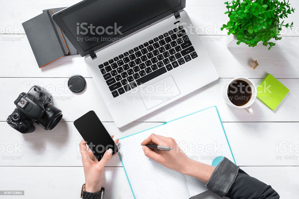 Flat lay, top view office table desk. Workspace with girl's hands, laptop, green flower in a pot, mint diary, coffee mug stock photo