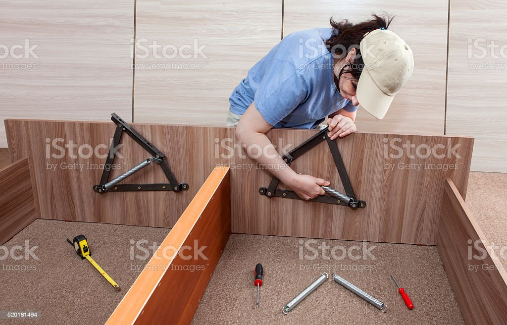 Flat Pack furniture assembly and installation service, women handyman working. stock photo