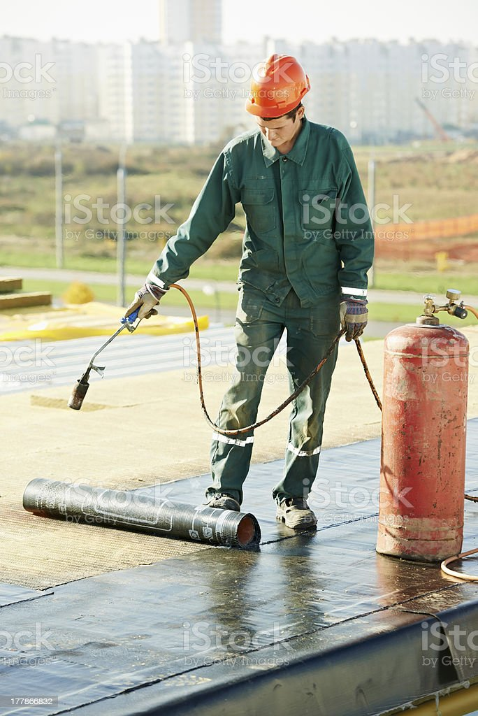 Flat roof covering repair works with roofing felt royalty-free stock photo