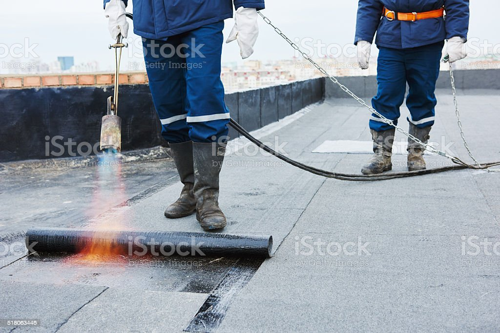 Flat roof installation. Heating and melting bitumen roofing felt stock photo