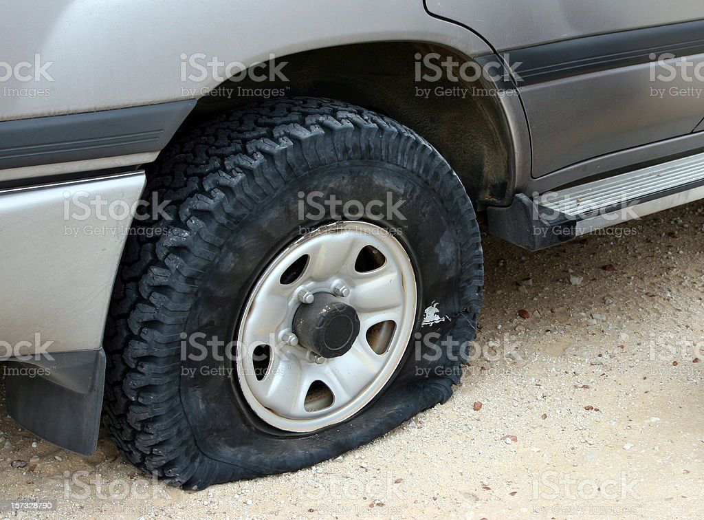 A flat tire deflating on an unpaved road stock photo