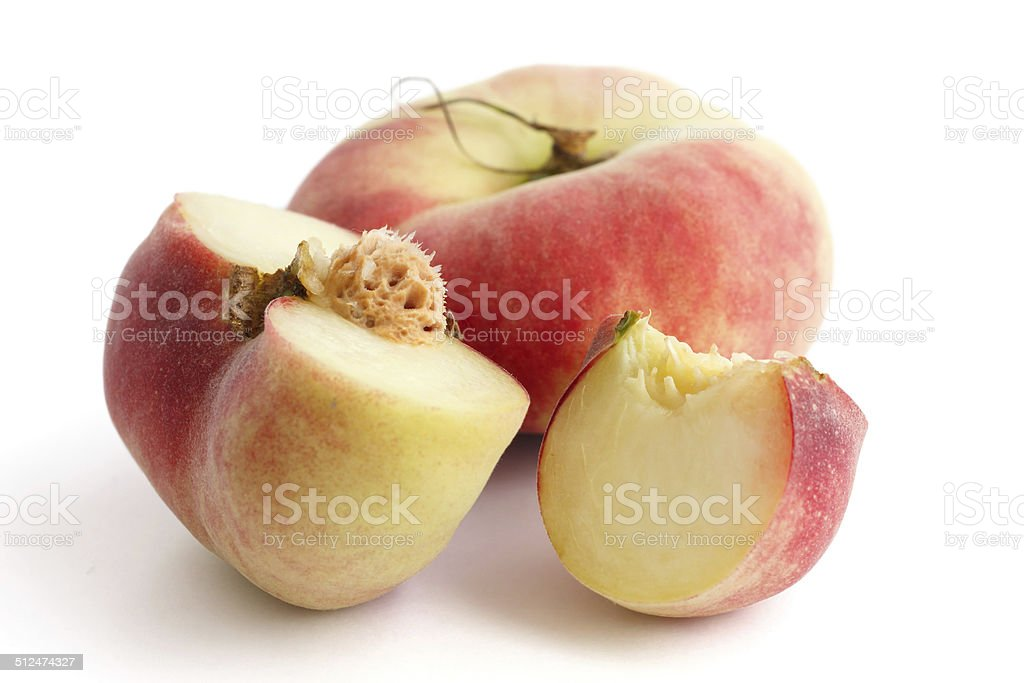 Flat white peach cut open with pip showing. stock photo