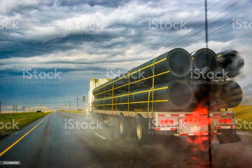 flatbed tractor trailer semi-truck under ominous dark stormy dramatic sky stock photo