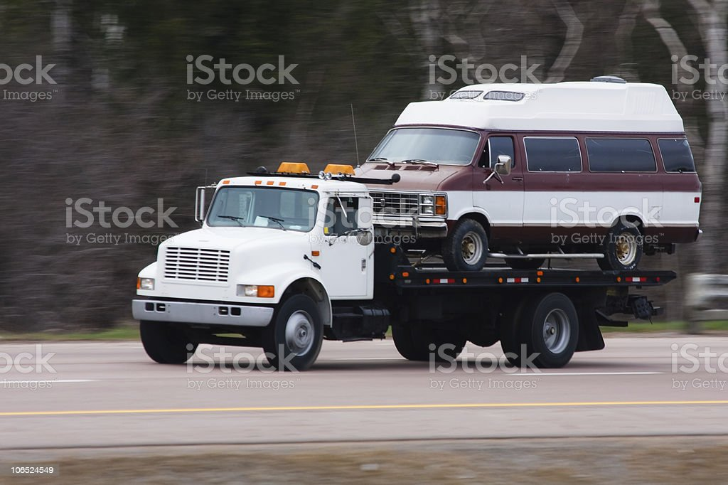 Flatbed truck transporting a van stock photo