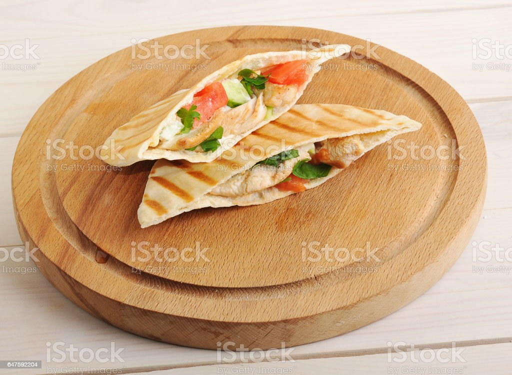 flatbread pita filled with chicken breast, vegetables and sauce stock photo