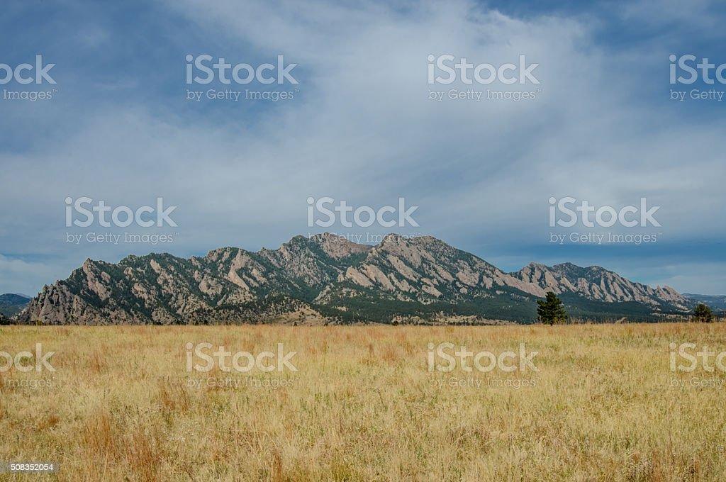 Flatiron Mountains with Dry Grassy Field stock photo