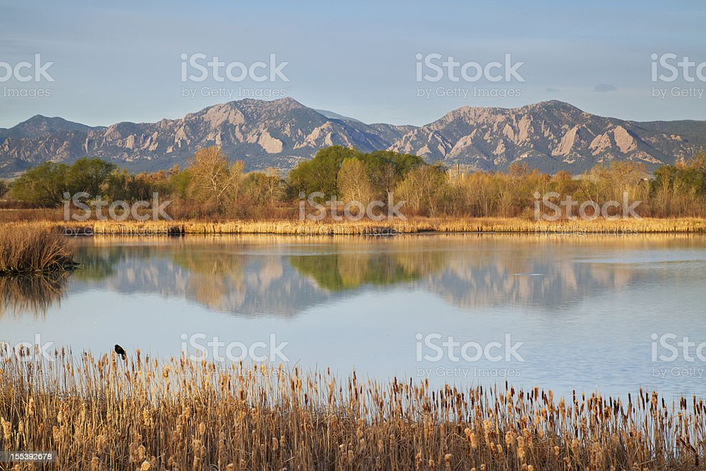 Flatirons at dawn reflecting in lake stock photo