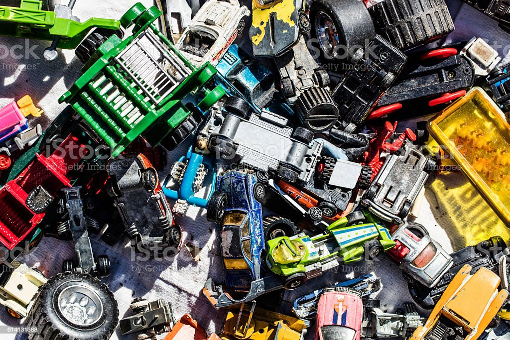 flatlay of car toys at garage sale for over-consumption stock photo