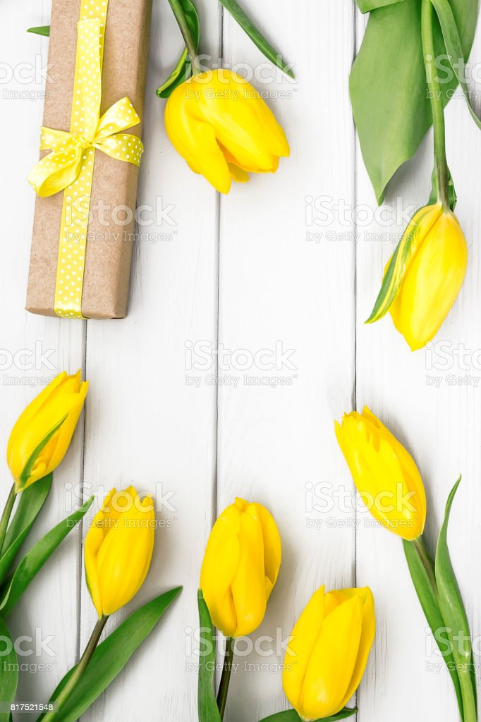 Flatlay with yellow tulips and gift present in craft paper stock photo