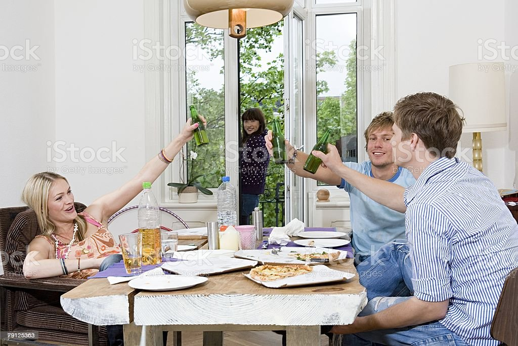 Flatmates having pizza and beer royalty-free stock photo