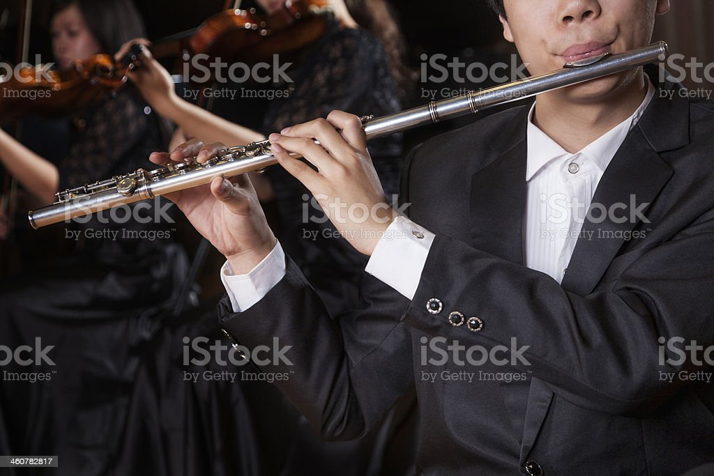 Flautist holding and playing the flute during a performance, close-up stock photo