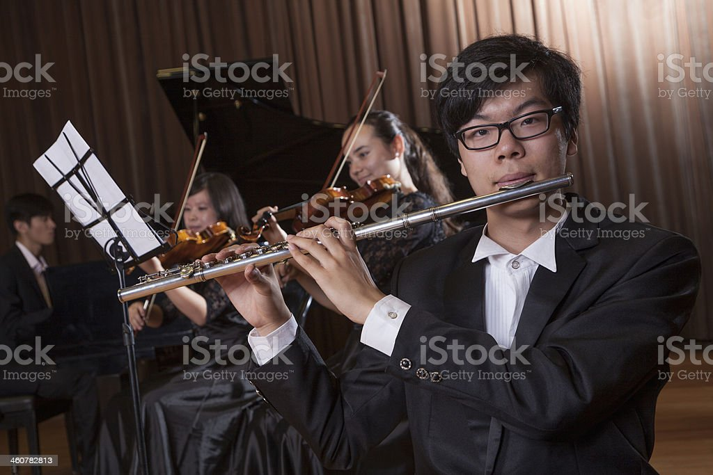 Flautist holding and playing the flute during a performance stock photo