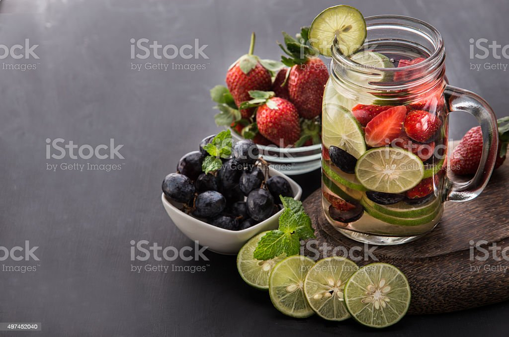 Flavored water mix with strawberries, lime, grape and mint leaves stock photo