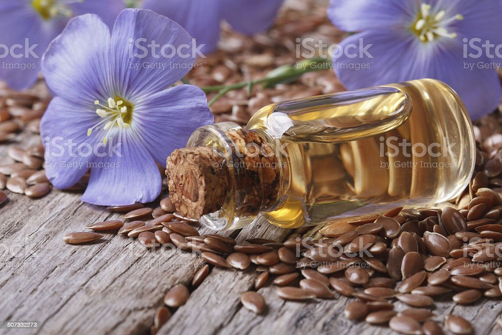flax seeds, blue flowers and oil close-up horizontal stock photo