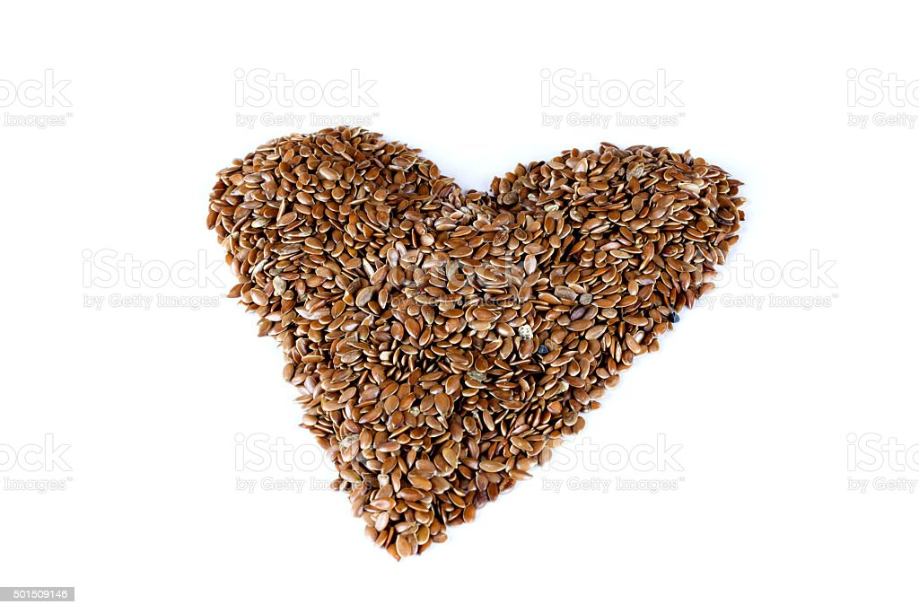 flax seeds in heart shape on isolated white background stock photo