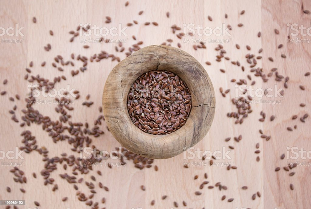 Flax seeds in olive wood bowl on wooden plate stock photo