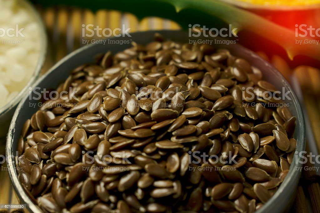 Flaxseed in a bowl with aloe and rice background, healthy stock photo