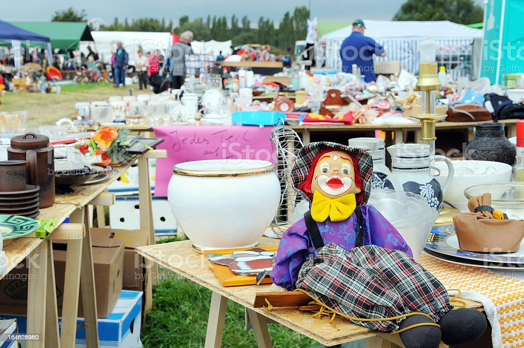 Flea Market with tables of clown marionette and dishware royalty-free stock photo