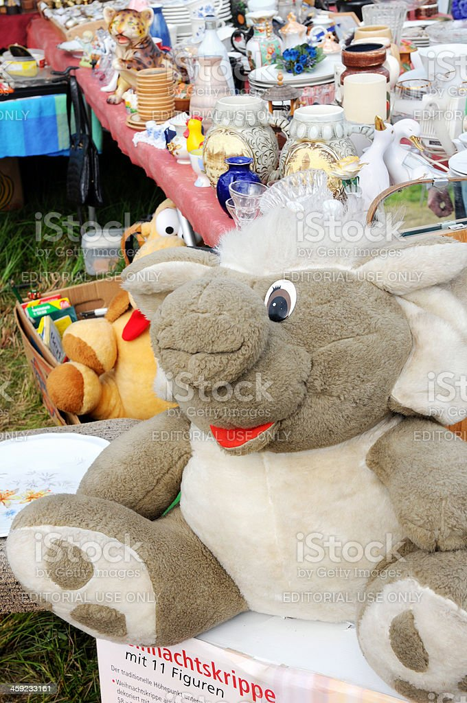 Flea Market with tables of dishware and big toy elephant stock photo