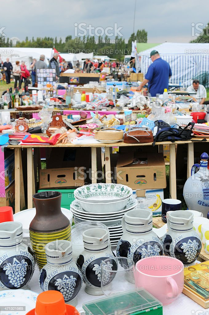 Flea Market with tables of dishware and visitors in background stock photo