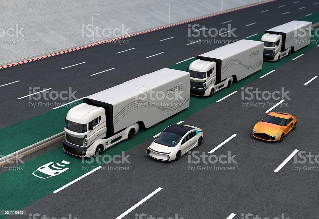 Fleet of autonomous hybrid trucks driving on wireless charging lane stock photo