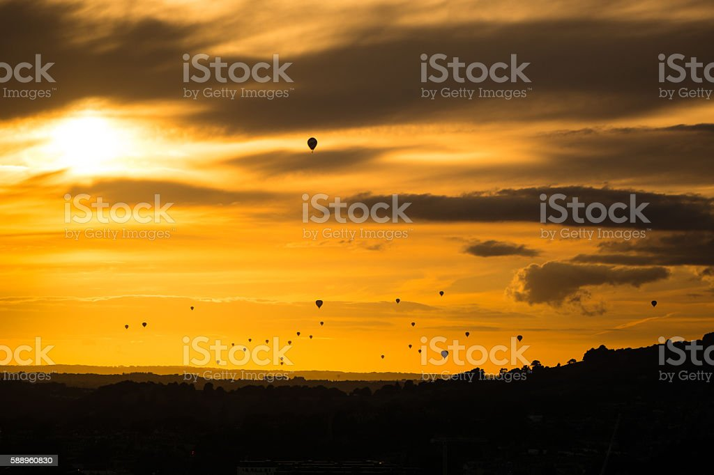 Fleet of hot air balloons in front of sunset stock photo
